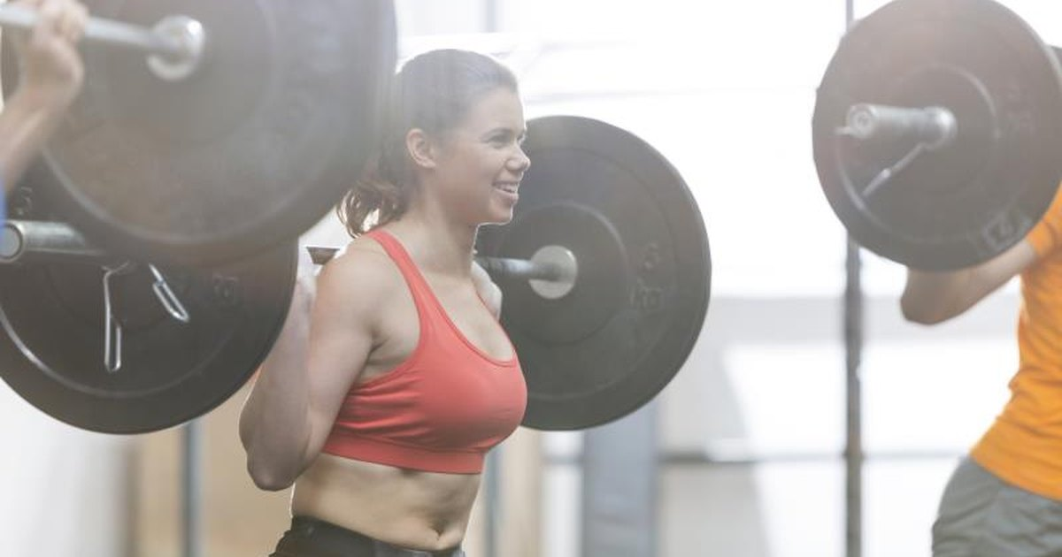Young Beautiful Fitness Exercising With Dumbbells In Gym