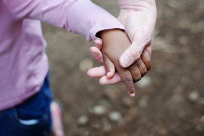 woman holding adopted child's hand