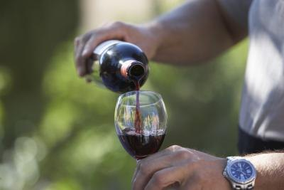 A man pours a glass of red wine.