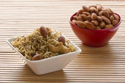 A bowl of brown rice with toasted cashews and almonds.