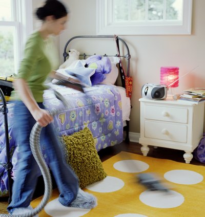 Girl vacuuming her bedroom