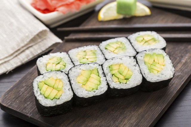 Avocado rolls on a plate next to chopsticks. Photo Credit VankaD ...