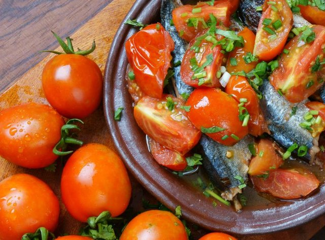 plate of steamed tomatoes next to a bunch of raw tomatoes. Photo ...