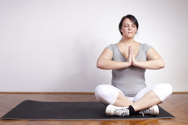Overweight woman sitting on a yoga mat meditation
