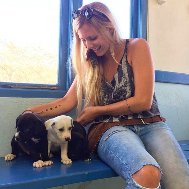 Rachel Brathen plays with puppies at the shelter she runs with her husband, Sgt. Pepper's Friends.