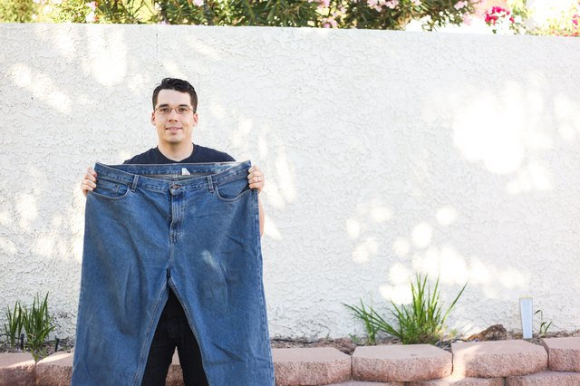 Mikal holds pants that are now too large for him.