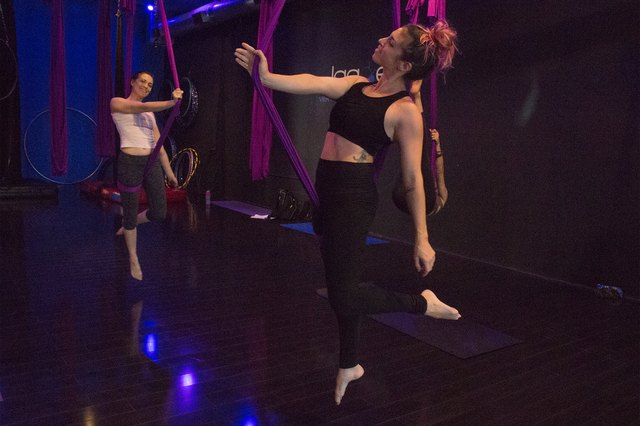 Jagged Vertical Dance and Fitness studio owner Jessica Anderson-Gwin (center) demonstrates aerial hammock poses.