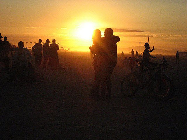 Two people embrace at sunrise at Burning Man 2008 near the Temple.
