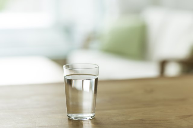 A glass of water on a table in a living space.