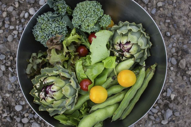 A variety of fresh picked garden vegetables in a galvenized bucket.