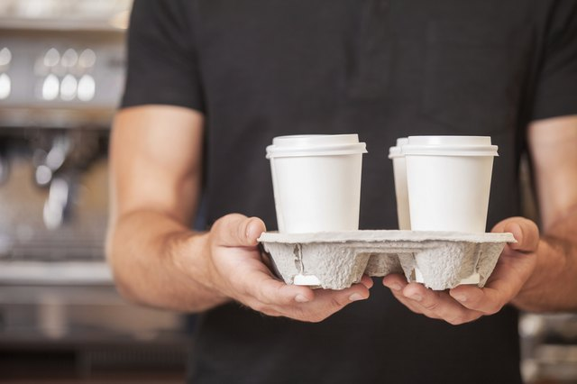 man carrying coffee to-go cups