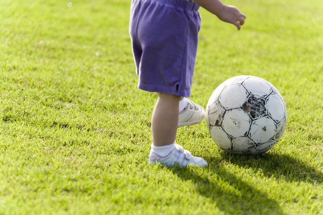 A young toddler kicks a soccer ball on the lawn.