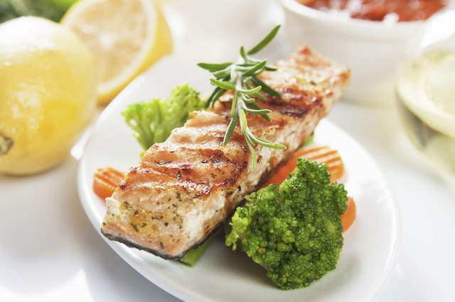 grilled salmon steak on a plate with broccoli and carrots