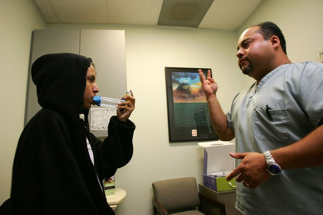 Asthma program director teaching a young patient how to use a new inhaler.