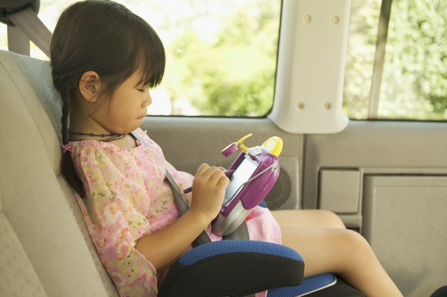 A girl sits in a booster seat without a backrest while playing with an electronic toy.