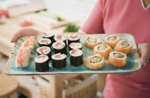 A woman holds a tray of sushi rolls.