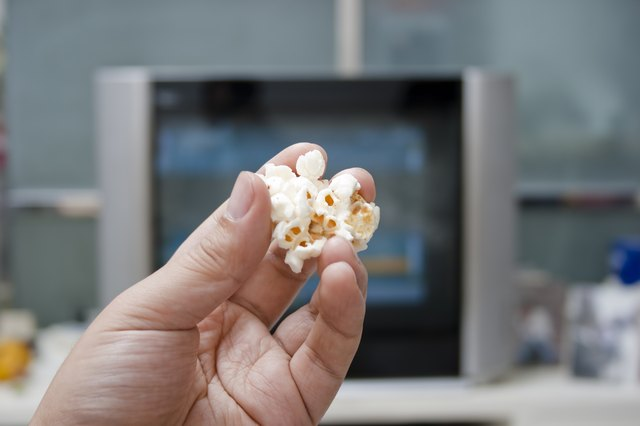 A person holds a kernal of popped popcorn in front of the television.