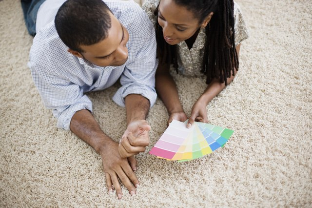 A couple looks at paint color swatches on the carpet.