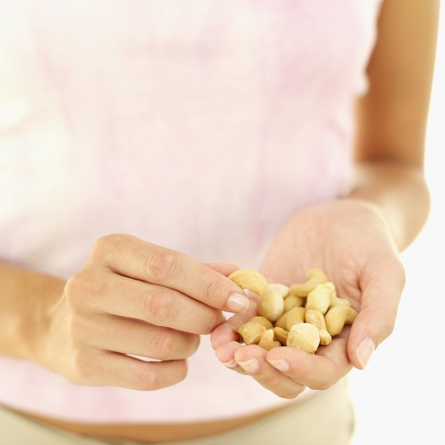 Young woman holding cashews in her hand.