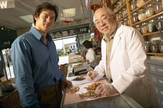 A man talks to an herb specialist in a herbal supplement shop.