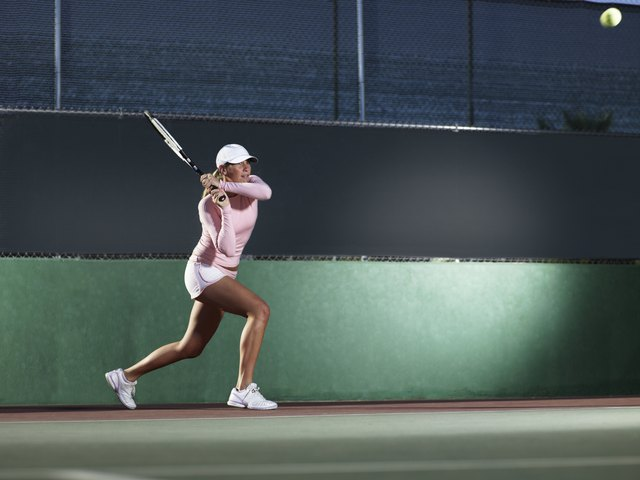 Woman tennis player hits a backhand
