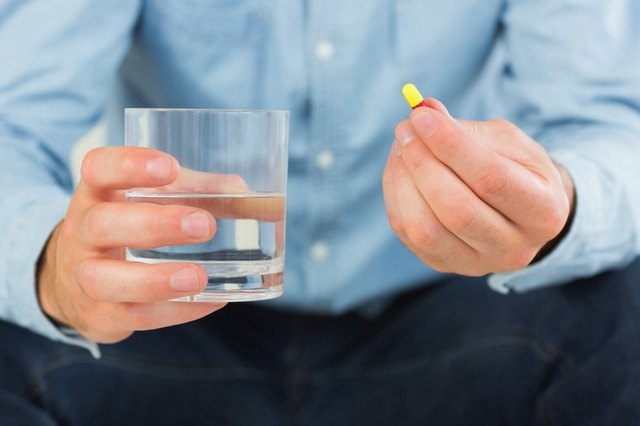 Close-up of man holding a glass of water and an antibiotic.