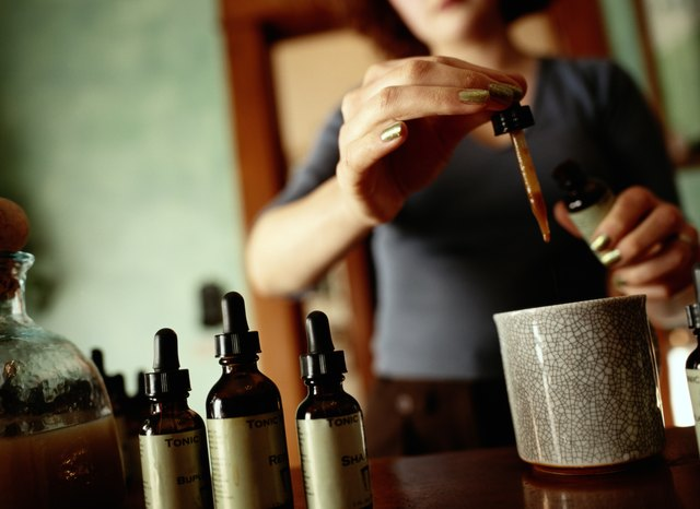 A chinese herbalist dispenses an herbal tonic from a dropper.