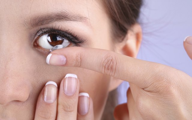 A woman is putting a contact lens in.