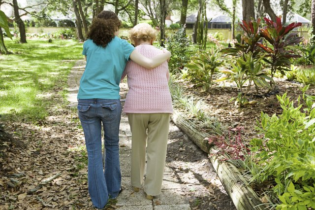Young woman helping her grandmother walk down a wooded path