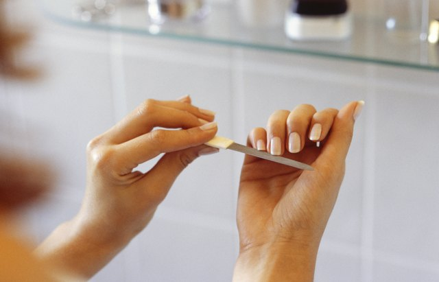 A woman cleans and files her fingernails with an emery board.