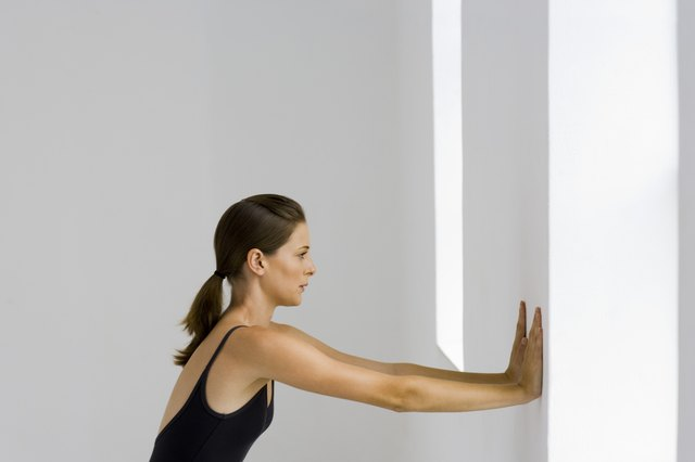 A woman is pushing her arms against a wall.