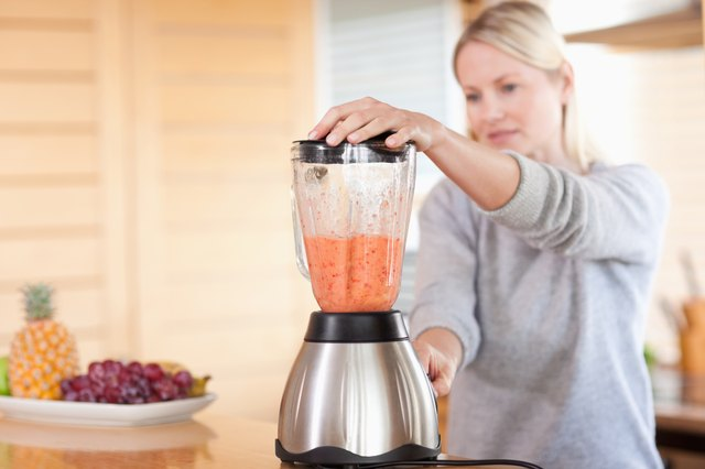 Woman blending a fruit smoothie
