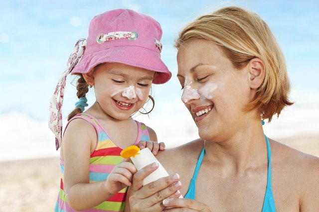 mother and child applying sunscreen