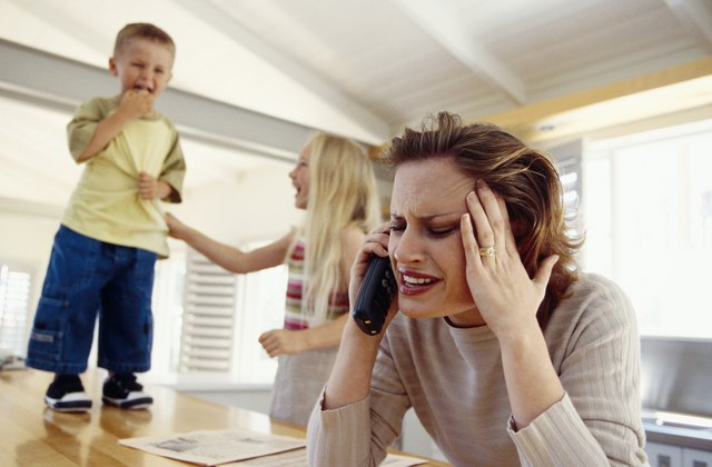A woman tries to talk on the phone with her children in the room.