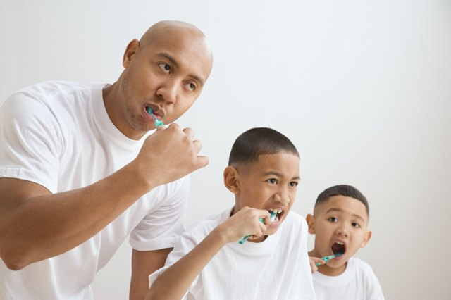 Dad and sons brushing teeth