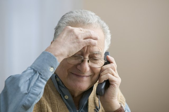 Senior man holding phone up to his ear.