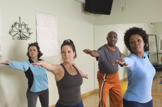 Four people in the Warrior II position in a yoga studio.