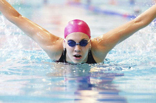 Woman performing butterfly stroke in pool