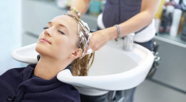woman having conditioner washed out of hair