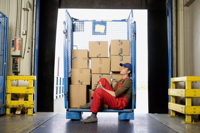 A worker is sitting in a delivery bay.