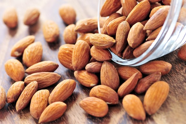 Almonds spilling from a glass bowl