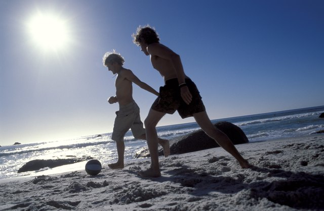 A group of friends play soccer on the beach.