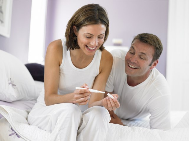 A couple on a bed looking at the results of a pregnancy test.