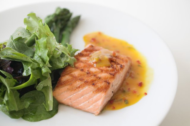 Close up of grilled salmon and a salad on a plate.