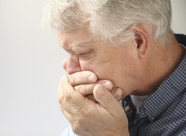 A senior man holding his mouth, experiencing nausea