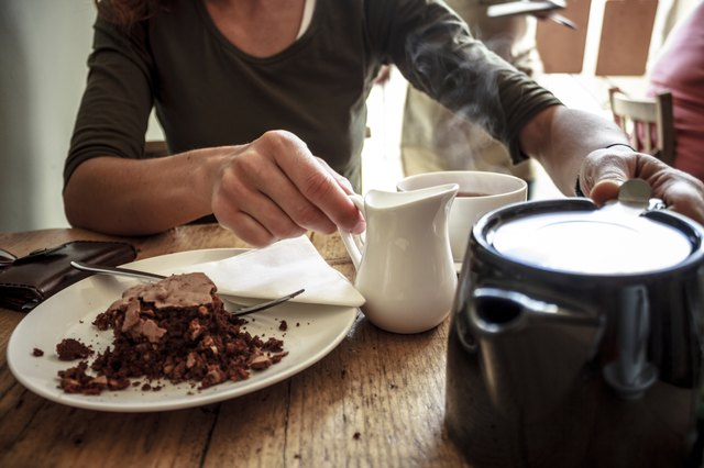 Woman eating cake and adding milk to coffee