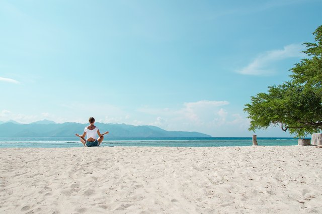 Simply watching someone do yoga on a beach is relaxing.