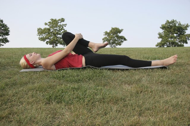 Woman doing knee-to-chest stretch