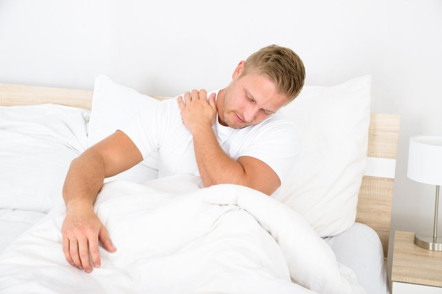 Man sitting in bed holding his shoulder