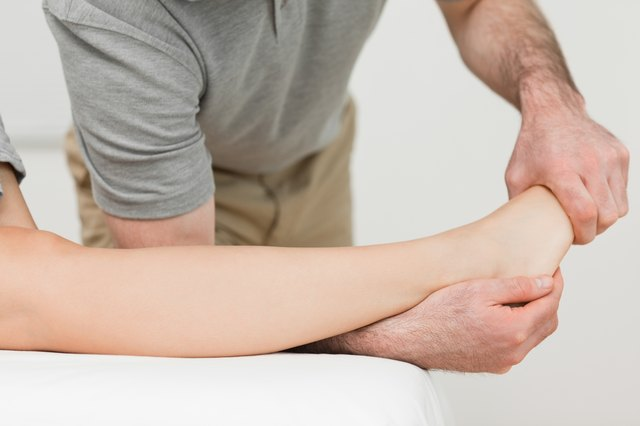 Physical therapist stretching a patient's ankle